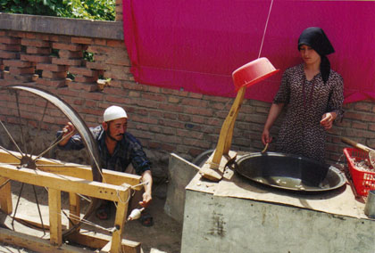 Chinese man and wife making silk